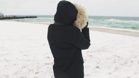Ung härlig kvinna som tar bilder av havet på en kall vinterdag långsam rörelse arkivfilmer