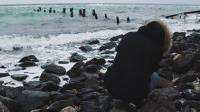 Ung härlig kvinna som tar bilder av havet på en kall vinterdag långsam rörelse stock video
