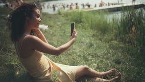 Ung härlig kvinna som tar selfie på telefonen, medan sitta på gräs lager videofilmer