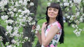 Ung härlig kvinna som tycker om lukten av det blommande trädet på en solig dag lager videofilmer