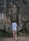 Ung härlig kvinna som vänder mot den forntida höga heliga statyn arkivbild