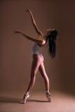 Ung härlig kvinnabalettdansör som poserar på tår över beiga arkivbilder