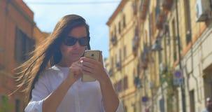 Ung härlig kvinnabrukssmartphone i den europeiska staden arkivfilmer