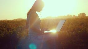 Ung härlig kvinnamaskinskrivning på en bärbar dator utomhus på härligt solnedgångsammanträde på gräset med den fantastiska lenses Arkivfoton
