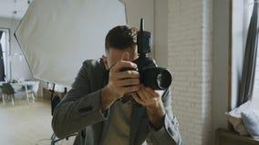 Ung härlig kvinnamodell som poserar för fotograf, medan han skjuter med en digital kamera i fotostudio inomhus stock video