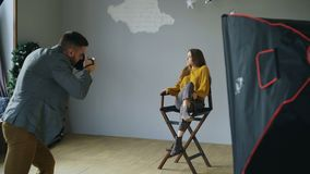 Ung härlig kvinnamodell som poserar för fotograf, medan han skjuter med en digital kamera i fotostudio inomhus arkivfilmer