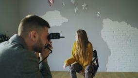 Ung härlig kvinnamodell som poserar för fotograf, medan han skjuter med en digital kamera i fotostudio inomhus lager videofilmer