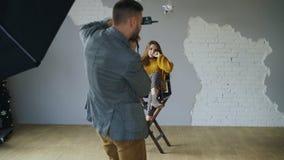 Ung härlig kvinnamodell som poserar för fotograf, medan han skjuter med en digital kamera i fotostudio inomhus Fotografering för Bildbyråer