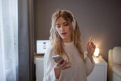 Ung härlig kvinnamusikvän Stående av den attraktiva flickan i hörlurar med telefonen, apps för att lyssna till musik royaltyfri fotografi