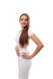 Ung härlig kvinnlig modell i den vita klänningen på grå bakgrund Arkivfoto