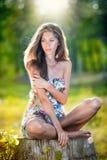 Ung härlig lång hårkvinna som bär en mångfärgad klänning som poserar på en stubbe Arkivfoto