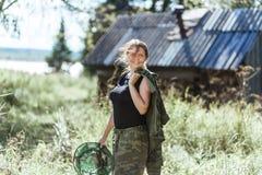 Ung härlig landskvinna i kamouflagedräkten som upptäcker naturen i skogbyn med myggnät Resor Arkivfoto