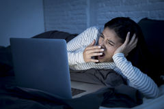 Ung härlig latinamerikansk internetknarkarekvinna på säng med tröttat att gäspa för datorbärbar dator Arkivfoto