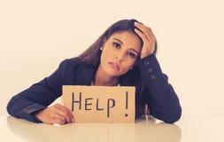 Ung härlig latinsk affärskvinna som förkrossas och tröttas rymma ett hjälptecken se belastat, uttråkat, frustrerat, upprivet och royaltyfri fotografi