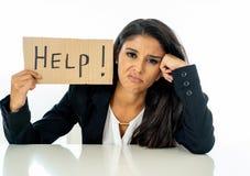 Ung härlig latinsk affärskvinna som förkrossas och tröttas rymma ett hjälptecken se belastat, uttråkat, frustrerat, upprivet och fotografering för bildbyråer