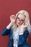 Ung härlig le blond flicka med härligt utseende och långt hår Le flickan i exponeringsglas och en charmig blick Royaltyfri Foto