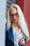 Ung härlig le blond flicka med härligt utseende och långt hår Le flickan i exponeringsglas och en charmig blick Royaltyfria Foton