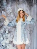 Ung härlig le flickastående i den snöig skogen för vinter, snöjungfru arkivfoto