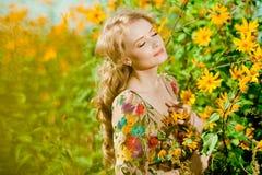 Ung härlig le kvinna i den blommande trädgården med blomman Arkivfoto