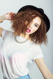 Ung härlig lycklig kvinna i en svart hatt, ljus makeup, lockigt hår, modefotografistudio på vit bakgrund Royaltyfri Foto