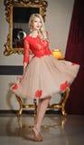 Ung härlig lyxig kvinna i elegant klänning. Härlig ung blond kvinna med en spegel i bakgrund. Förförisk blond kvinna Arkivbild