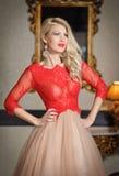 Ung härlig lyxig kvinna i elegant klänning. Härlig ung blond kvinna med en spegel i bakgrund. Förförisk blond kvinna Arkivfoto