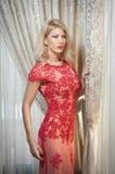 Ung härlig lyxig kvinna i lång elegant klänning. Härlig ung blond kvinna i röd klänning med gardiner i bakgrund Royaltyfri Bild