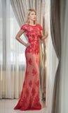 Ung härlig lyxig kvinna i lång elegant klänning. Härlig ung blond kvinna i röd klänning med gardiner i bakgrund Royaltyfri Foto