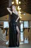Ung härlig lyxig kvinna i lång elegant svart klänning. Härlig ung blond kvinna med ljusa ljus i bakgrund Royaltyfri Fotografi