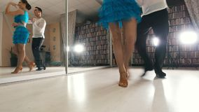 Ung härlig man- och kvinnadans och praktiserande latin - amerikansk dans i dräkter i studion, fokus på fot arkivfilmer