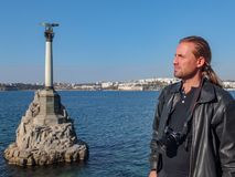 Ung härlig manfotograf med blont långt hår i svartläderomslag med kameran mot Black Sea i rätt från monumentet royaltyfri fotografi