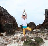 Ung härlig manmeditation på stranden Royaltyfri Bild