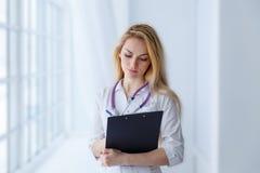 Ung härlig medicinsk doktor som skriver ett recept i klinik Royaltyfria Foton