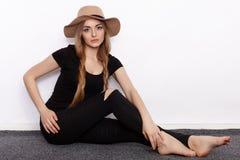 Ung härlig modemodell i för t-skjorta för kvinnor som sönderriven jeans för svart svart moderiktig hatt poserar att sitta barfota Royaltyfri Fotografi