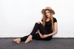 Ung härlig modemodell i för t-skjorta för kvinnor som sönderriven jeans för svart svart moderiktig hatt poserar att sitta barfota Arkivbilder