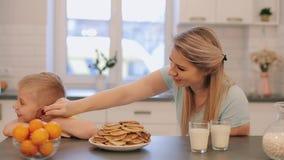 Ung härlig moder i blåa skjortor som har gyckel med hennes son i gul skjorta på köket Mamman matar hennes sonpannkakor lager videofilmer
