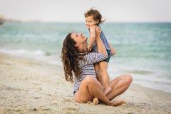 Ung härlig moder och hennes förtjusande son som har gyckel på stranden fotografering för bildbyråer
