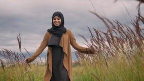 Ung härlig muslimkvinna i hijab som trycker på växter i fält med hennes hand som går till och med äng stock video
