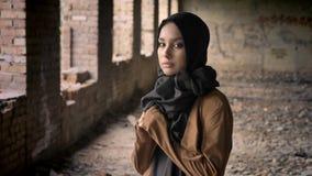 Ung härlig muslimkvinna, i svart hijabanseende i övergiven byggnad och att se kameran med förskräckt och stock video