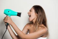 Ung härlig naken flicka i handduk som sjunger med hårtork royaltyfri bild