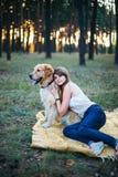Ung härlig och le flicka som spelar med en hund Royaltyfri Bild