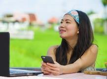 Ung härlig och lycklig asiatisk digital nomad eller turist- kvinnanätverkande för kines utomhus med den bärbar datordatoren och m arkivfoton