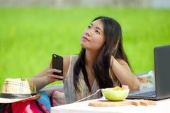 Ung härlig och lycklig asiatisk digital nomad eller turist- kvinnanätverkande för kines utomhus med den bärbar datordatoren och m royaltyfria foton