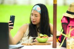 Ung härlig och lycklig asiatisk digital nomad eller turist- kvinnanätverkande för kines utomhus med den bärbar datordatoren och m royaltyfria bilder