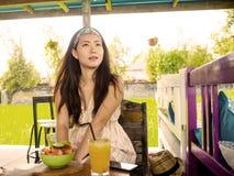 Ung härlig och lycklig asiatisk kinesisk kvinna som dricker orange fruktsaft som utomhus äter sund sallad på enjoen för coffee sh arkivfoto