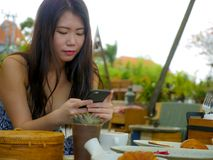 Ung härlig och lycklig asiatisk koreansk kvinna som använder socialt massmedia app för internet på mobiltelefonen som ler gladlyn arkivbild
