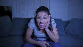ung härlig och lycklig latinsk kvinna på hennes 30-tal som rymmer TVfjärrkontrollen som tycker om den hållande ögonen på TV-progr royaltyfri fotografi