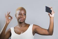 Ung härlig och lycklig svart afro amerikansk kvinna som ler den upphetsade tagande selfiebildståenden som ok ger att blinka för h arkivfoto