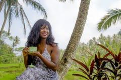 Ung härlig och lycklig svart afro amerikansk turist- kvinna som dricker kaffe eller te som besöker djungelkolonin i Thailand elle Arkivfoton