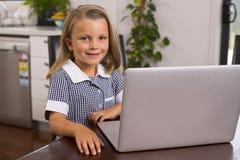 Ung härlig och söt liten flicka 6 till 8 gamla år med blont hår och blåa ögon som sitter hemmastatt kök som tycker om med bärbara Arkivfoton